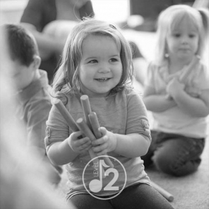 A young girl participates in music class for toddlers.