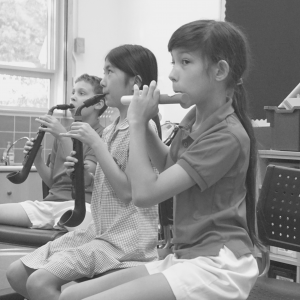 Three girls attend a woodwind music class.