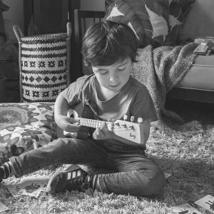 A boy participates in guitar classes for children.
